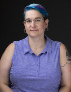 Head shot of a woman in a purple sleeveless shirt with peacock colored hair.